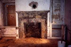 an old stone and brick fireplace with chipping white paint and wall pieces - before
