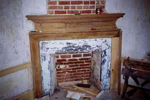 an old fireplace made of damaged brick and stone - before