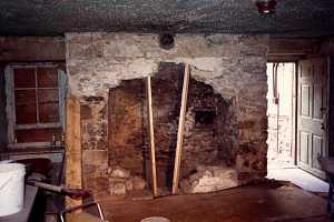 an old stone fireplace being opened up through removal of stone