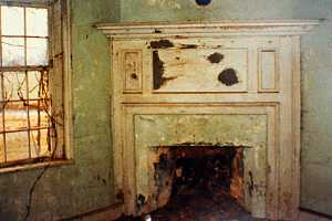 an old fireplace area with vines growing in the window beside it - before