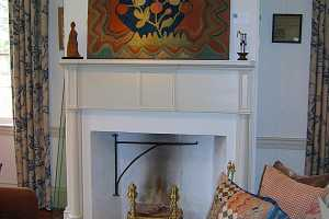 a fireplace area with a decorative painting above it