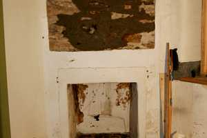 a damaged wall and fireplace area - before