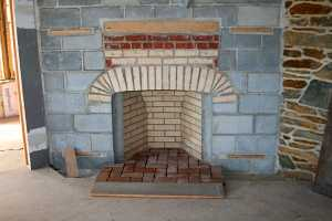 a fireplace of bricks in between a cinder block wall - before