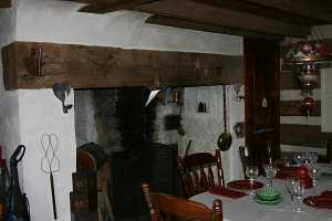 fireplace behind a kitchen table set for dinner