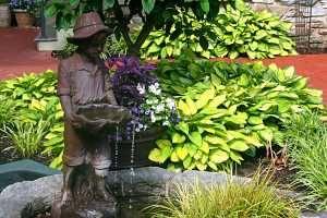 a small boy water fountain in a fish pond next to a decorative planter and shrubs
