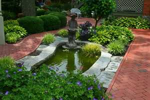 a fish pond with a small boy statue on the edge and some water plants and fish in it