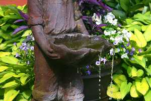 a small boy water fountain in a fish pond next to a decorative planter and in front of some green and yellow hostas
