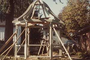 a wooden gazebo with framing posts and the top framed out