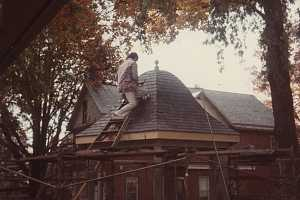 a man putting the roof on a gazebo