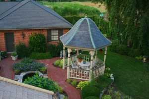 a brand new gazebo complete with a brick walkway, fish pond, furniture and gardens