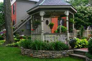 a gazebo surrounded by a beautiful landscape with shrubs, stone walls and other features
