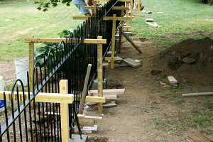 two men installing a black iron fence