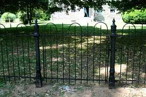 a black iron fence in front of a stone home
