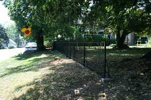 a newly installed black iron fence