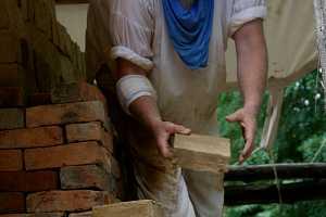 a man in white stacking bricks