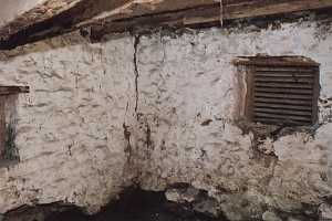 The inside of an old stone spring house in poor shape