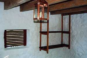 A lantern and shelving in a restored spring house