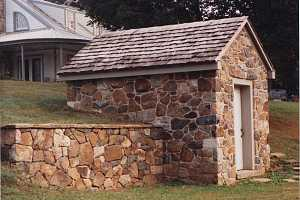 A restored stone spring house built into a hill
