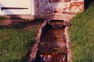 Water flowing out of a stone spring house built in 1989