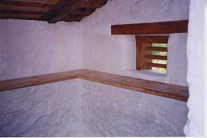 The inside corner of a restored spring house looking at shelving and a window