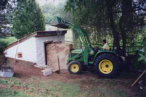 A green John Deere tractor moving a slab of stone into a restored spring house