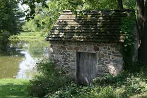 A restored stone spring house next to a pond
