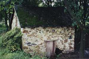 An old stone spring house with some stone missing