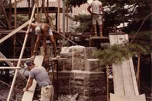 Workers developing scaffolding in preparation for custom stone transport to an archway
