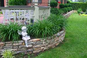 a stone retaining wall wrapped around a brick home with an angel sitting on it and plants behind it
