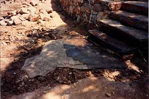 a stone retaining wall and stone steps leading down to a flagstone landing