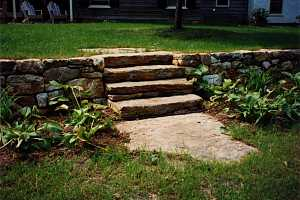 a stone wall and steps with a stone landing - completed