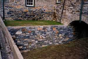 a brand new stone retaining wall under a bridge and leading to a tunnel - after