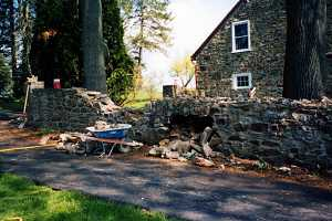 a stone wall that is falling apart with a wheel barrow in front a stone house behind