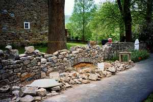 the rebuilding of a stone wall. dozens of stones lay in front with two buckets