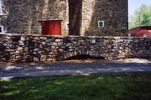 a rebuilt stone wall next to a driveway beside a stone home