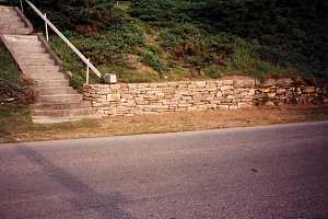 a newly completed section of a stone retaining wall with a mailbox sitting on the ledge
