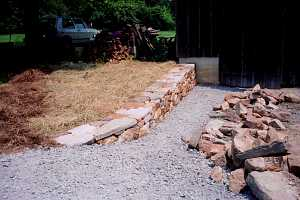 a stone retaining wall newly installed with fresh road stone in front of it