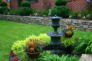 a fountain with a stone retaining wall and plants behind it