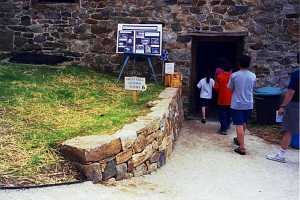 a stone retaining wall leading into a door. a sign on the hill reads grist mill guided tours