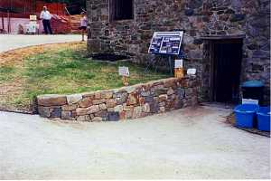 stone retaining wall leading into a stone building. a sign on the hill reads grist mill guided tours