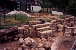 a stone wall and step installation in progress along with a backyard transformation