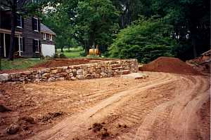 a yard that's been leveled with dirt and had a stone wall and stairs installed