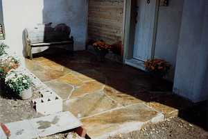 a stone patio with a bench and flowers on it