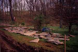 large stones waiting for a project in someones backyard. behind the stones are many trees