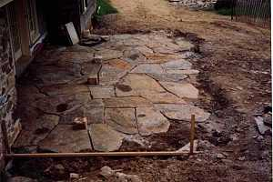 a dug-out section of yard where a stone patio is being installed