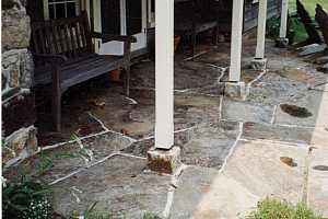a stone patio with pillars and benches sitting on it