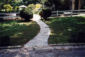 a twisted stone walkway running from a driveway to the backyard between two evergreens and a white fence