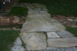 a stone walkway with grass growing between the stones