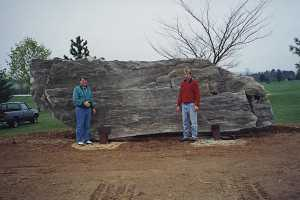 two men standing in front of a large stone