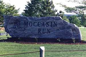 a large stone sign that reads moccasin run with a logo engraved in the stone and a flowerbed in front
